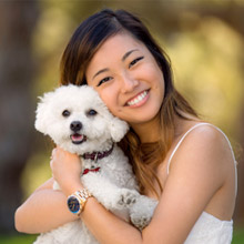 Woman with bright white smile hugging her dog
